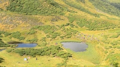 Group of people near two lakes in Carpathians in late summer - stock footage
