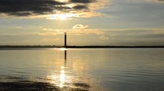 Water landscape with lighthouse and clouds during daybreak Stock Footage