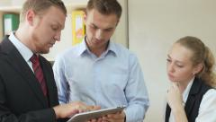 Top Manager talk to young active members of the works showing tablet computer Stock Footage