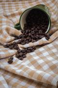 Cup full of coffee beans on cotton Stock Photos