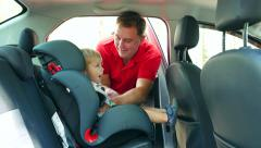 Male takes out a kid baby boy toddler from child car seat Stock Footage