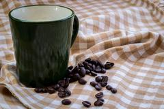 Cup full of coffee beans on cotton - stock photo