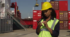 Businesswoman talking on a mobile phone at a commercial dock. Shot on RED Epic. Stock Footage