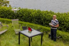Drone Operator flying a drone - seen from the side - stock photo