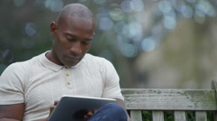 4K Smiling casual man looking at computer tablet in urban park area Stock Footage