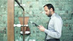 Young businessman with tablet computer checking his appearance in bathroom Stock Footage