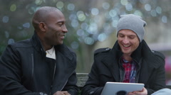 4K Happy casual male friends looking at computer tablet in urban park area Stock Footage