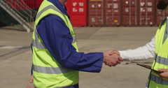 Dock workers shake hands and discuss shipping logistics in a shipyard. - stock footage