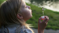 Beautiful little girl inflates soap bubbles in the park Stock Footage