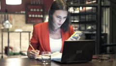 Busy businesswoman working by table in kitchen at night Stock Footage