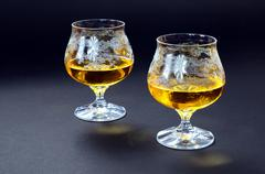 Two glasses of cognac on a black background - stock photo