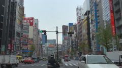 Traffic car busy road Shinjuku district Tokyo crowded downtown people commute  Stock Footage