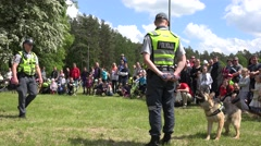 Policeman in uniform with trained dog performance for people audience. 4K Stock Footage