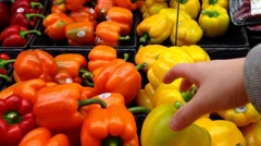 Woman selecting yellow peppers in grocery store - stock footage