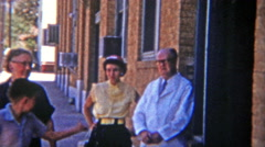 1955: Small town doctor walking with family on main street. Stock Footage