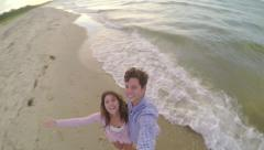 Cute Couple Use Gopro Stick On Beach, They Spin In Circle And Smile Stock Footage