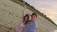 Cute Couple Walk Down Beach, Using Gopro Stick, Woman Puts Arm In Air - stock footage
