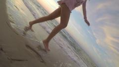 Perspective Of Young Woman's Legs As She Runs Along Beach, Using Gopro Stick Stock Footage