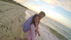 Woman Runs With Gopro Stick, Her Boyfriend Catches Up And Hugs Her, They Walk Stock Footage