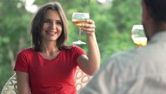 Young couple talking, raising toast and drinking beverages in cafe Stock Footage