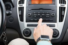 Close up of male hand turning on radio in car Kuvituskuvat