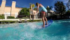 Stock Video Footage of Pool-girl jumps on surfboard slomo