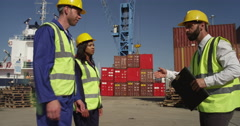 Dock workers shake hands and discuss shipping logistics in a shipyard. Stock Footage