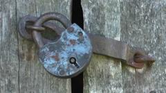 Locking Unlocking  padlock an old rustic door Stock Footage