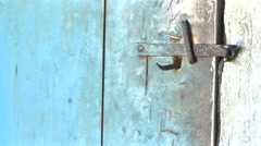 Key unlocking an old rustic door latch. - stock footage