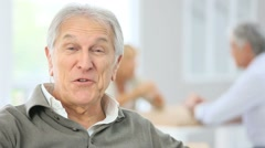 Senior man speaking to camera, people in background - stock footage