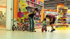 Mall Parents pick up his son, the first two-wheeled bicycle in baby shop - stock footage