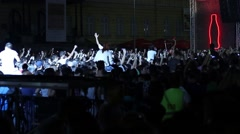 Pop a huge crowd of cheering spectators highlighted concert spotlights - stock footage
