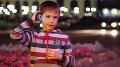 Small handsome boy 8 years old, talking on mobile phone at night in the city Stock Footage