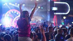 Pop The little girl on his shoulders raises his hands in concert with selfie Stock Footage