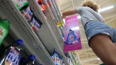 Woman in Supermarket Choosing Household Goods Stock Footage