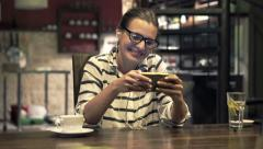 Young, happy woman watching movie on smartphone in kitchen at night Stock Footage
