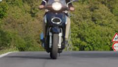 Front view of young male riding a scooter over a hill toward camera Stock Footage