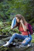 Young European woman hiker by the river, outdoors activities - stock photo