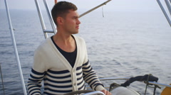 Young man is driving a sailing boat in the sea Stock Footage