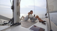 Young couple relaxing on a sailing boat in the sea at sunset Stock Footage