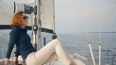 Beautiful woman in sunglasses is relaxing on a yacht in the sea - stock footage