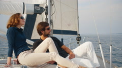 Couple in sunglasses are relaxing on a sailboat in the sea - stock footage
