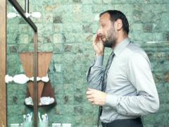 Young businessman cleaning face with cotton swab in bathroom  NTSC Stock Footage