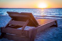Sunbed on the beach at sunset Stock Photos