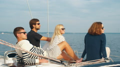 Group of people in sunglasses are relaxing on a sailboat Stock Footage