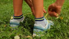 Kid tying shoe in the park and running Stock Footage