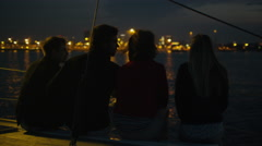 Group of people relaxing on a yacht in the sea at night - stock footage