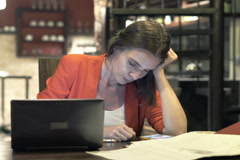 Tired businesswoman sleeping on wooden table at home at night NTSC Stock Footage
