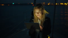 Girl is using a tablet on a sailing boat in the sea at night - stock footage