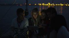 Group of people are using tablet on a sailing boat in the sea at night - stock footage